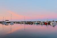 Commercial fishing boats docked in Menemsha Basin under a colorful pre-sunrise sky, in the fishing village of Menemsha in Chilmark, Massachusetts on Martha's Vineyard.