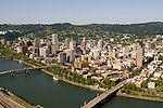 Aerial view looking southwest at downtown Portland with the Willamette river in the foreground.