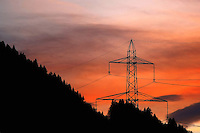 Silhouette of a high tension pole with forest and mystical sunset sky in the background