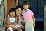 """THIS PHOTO IS AVAILABLE AS A PRINT OR FOR PERSONAL USE. CLICK ON """"ADD TO CART"""" TO SEE PRICING OPTIONS.   Mirjava Memetovic holds her daughters Kristina (left) and Laura, in front of their makeshift home in Palilula, a neighborhood of Belgrade, Serbia. They are Roma, also known as Gypsies, and were expelled in 2012 from the center of Belgrade to make way for new apartments and office buildings. Because Memetovic had no identity documents, she was sent with her daughters to her native village in the south of the country, but soon returned as she had no way to survive there. She and her daughters beg for money at a fast food restaurant near their squatter settlement."""
