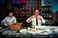 A Chinese herbalist preparing herbal prescriptions in his Chinatown shop in downtown Honolulu