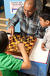 Afterschool chess program for elementary students graduates of Headstart program male teacher working with two boys