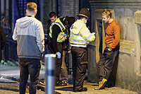 Pictured: A man is spoken to by police officers. Friday 14 December 2018<br /> Re: Revellers in Wind Street, Swansea, Wales, UK.