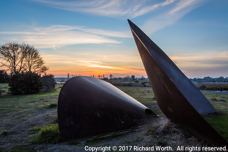 Sunset paints the horizon in the background, behind the Duplex Cone art installation at the Martin Luther King Jr. Regional Shoreline near the Oakland International Airport.