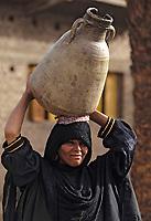 Afrique/Egypte/Env de Louxor/Ancienne Thèbes: Portrait de femme de dos - Vie du village - Transport de l'eau dans une jarre