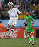 The USA's  Herculez Gomez heads the ball as Algeria's Nadir Belhadj looks on.  USA played Algeria in a 2010 FIFA World Cup first round match at Loftus Versfeld Stadium in Tshwane/Pretoria, South Africa on Wednesday, June 23, 2010. The USA defeated Algeria 1-0 to win Group C and advance to the second round of the 2010 FIFA World Cup.