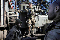 """UKRAINE, 02.2016, Novohrodivka, Oblast Donetsk. Ukrainian-Russian conflict concerning Eastern Ukraine / Foreign volunteers (""""Task Force Pluto"""") fighting with the far-right militia Pravyi Sektor against the Russian-backed separatists: An Ukrainian militia stands on a truck returning from the frontline to the base of the right-wing organisation. Alex (Austria) and Cowboy (USA) get ready to unload the truck. © Timo Vogt/EST&OST"""