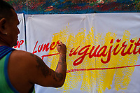 "José Corredor (""Runner"") writes with a brush while working on music party posters in the sign painting workshop in Cartagena, Colombia, 12 December 2017. Hidden in the dark, narrow alleys of Bazurto market, a group of dozen young men gathered around José Corredor (""Runner""), the master painter, produce every day hundreds of hand-painted posters. Although the vast majority of the production is designed for a cheap visual promotion of popular Champeta music parties, held every weekend around the city, Runner and his apprentices also create other graphic design artworks, based on brush lettering technique. Using simple brushes and bright paints, the artisanal workshop keeps the traditional sign painting art alive."