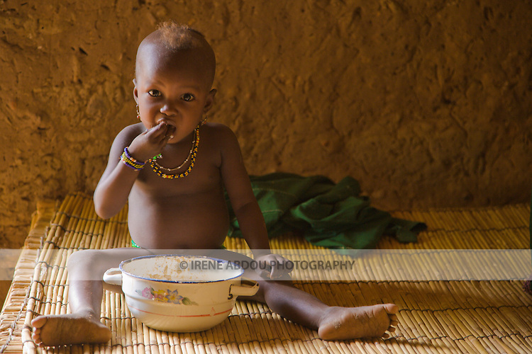 """A small child in the  village of Bele Kwara in southwestern Niger eats """"pot and sauce"""" with her hand in the typical traditional African manner. She sits atop a handmade millet stalk bed inside a mud hut."""