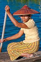 Myanmar, Burma.  Woman of Intha Ethnic Group Rowing her Canoe, Inle Lake, Shan State.