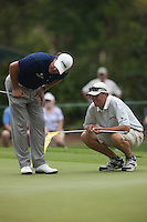 """PONTE VEDRA BEACH, FL - MAY 5: Phil Michelson and caddie Jim """"Bones"""" MacKay discuss a putt on the 12th green during his practice round on Tuesday, May 5, 2009 for the Players Championship, beginning on Thursday, at TPC Sawgrass in Ponte Vedra Beach, Florida."""
