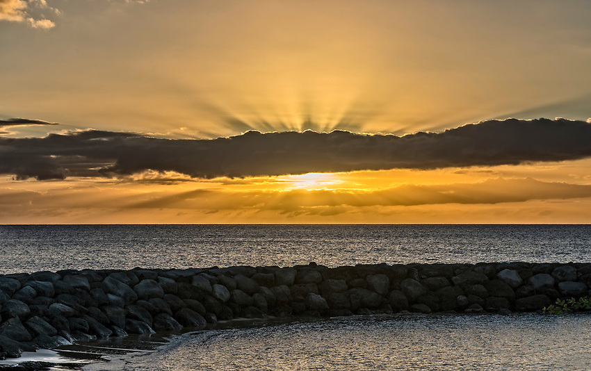 The sun shoots beams around clouds while descending to the horizon over the Pacific Ocean in Maui, as seen from the Kihei Boat Launch dock