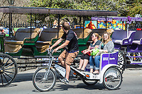 French Quarter, New Orleans, Louisiana.  Man-powered Tricycle-Taxi Passing by Jackson Square.