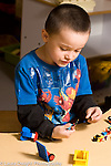Education Preschool 3-4 year olds boy playing with colored plastic Lego bricks talking to self vertical