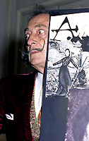 "portrait of Salvador Dali in his suite at hotel Maurice Paris,<br /> 1973<br /> <br /> <br />  - Salvador Domènec Felip Jacint Dalí i Domènech, Marquis de Púbol (May 11, 1904 – January 23, 1989), commonly known as Salvador Dalí  was a prominent Spanish Catalan surrealist painter born in Figueres.<br /> <br /> Dalí was a skilled draftsman, best known for the striking and bizarre images in his surrealist work. His painterly skills are often attributed to the influence of Renaissance masters.His best-known work, The Persistence of Memory, was completed in 1931. Dalí's expansive artistic repertoire includes film, sculpture, and photography, in collaboration with a range of artists in a variety of media.<br /> <br /> Dalí attributed his ""love of everything that is gilded and excessive, my passion for luxury and my love of oriental clothes to a self-styled ""Arab lineage,"" claiming that his ancestors were descended from the Moors.<br /> <br /> Dalí was highly imaginative, and also had an affinity for partaking in unusual and grandiose behavior. His eccentric manner and attention-grabbing public actions sometimes drew more attention than his artwork to the dismay of those who held his work in high esteem and to the irritation of his critics -"