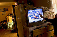 Wrestler Julia Pacena (fighting name), Remedios Condori Ajsara (real name) prepares a meal in her kitcken while her children watch wrestling on the television. Remedios is a Cholita, a wrestler of native Aymara descent. When Cholitas fight they wear traditional costume. Remedios fights with the lucha libre (free wrestling) group Los Diosas del Ring. ..