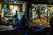 Fairy lights shine on a shop vendor waiting for customer in his shop in Anandopur in Kolkata, West Bengal, India.