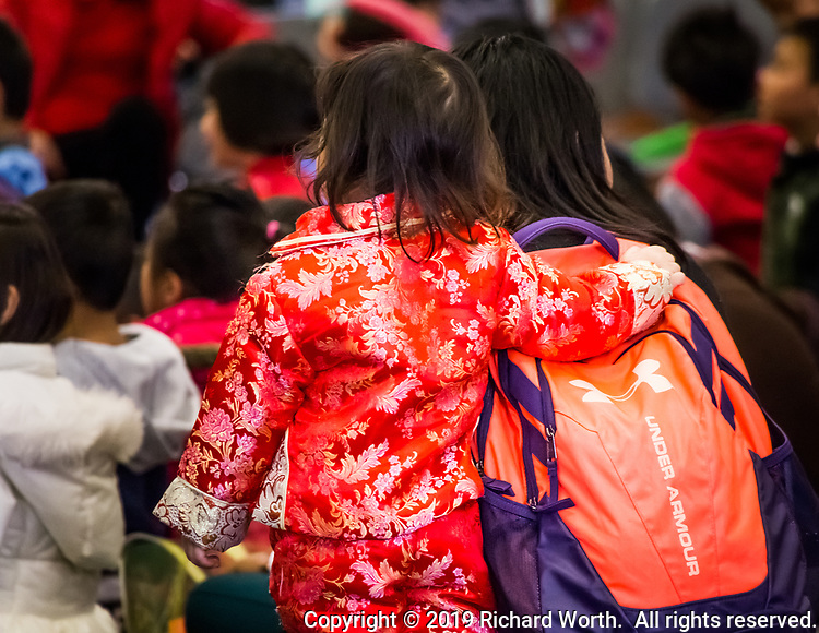 Mom and daughter share a moment during the Magic Show part of a Lunar New Year celebration