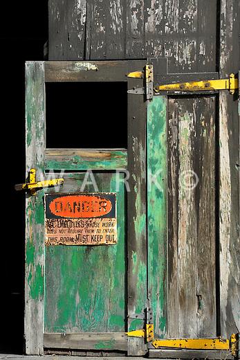 Danger sign on abandoned steel plant door.