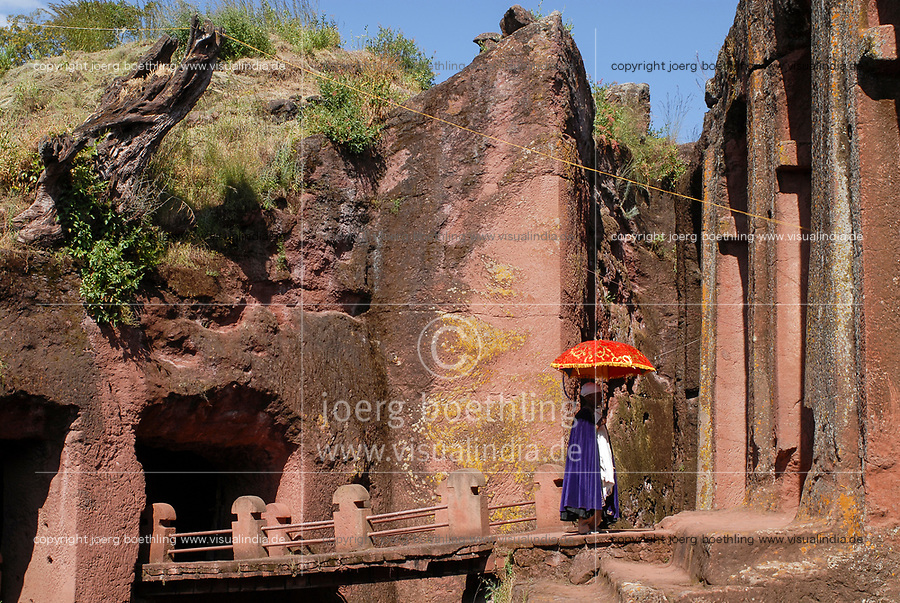 ETHIOPIA, Amhara region, Lalibela , monolith rock churches built by King Lalibela 800 years ago, Emmanuel church, Bet Emmanuel , priest with coloured umbrella / AETHIOPIEN Lalibela oder Roha, Koenig LALIBELI liess die monolithischen Felsenkirchen vor ueber 800 Jahren in die Basaltlava auf 2600 Meter Hoehe hauen und baute ein zweites Jerusalem nach, Emmanuel Kirche