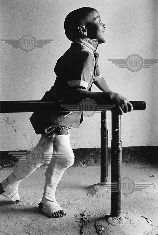 Hamish Wilson / Panos Pictures..SOMALILAND..Polio victim practising walking with splints.