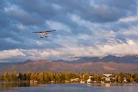 Bush plane approaches landing on floats along Lake Hood, Anchorage, Alaska.