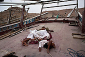 Sur, Oman<br /> July 2001<br /> <br /> Dhow builders sleep on the deck of dhows in the  construction harbor.