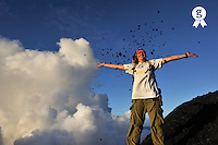 Woman throwing up lava stones nearby crater (Licence this image exclusively with Getty: http://www.gettyimages.com/detail/84430558 )