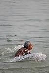 An Indian man taking a holy dip in the polluted dirty water of Ganga in Varanasi, Uttar Pradesh, India.