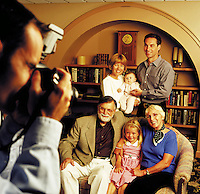 Three generations of a family have their portrait taken by a photographer.