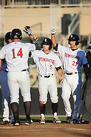 Corey Zangari (14) of the Kannapolis Intimidators is greeted at home plate by teammates Tyler Sullivan (5) and Seby Zavala (21) after hitting a 3-run home run against the Hagerstown Suns at Kannapolis Intimidators Stadium on May 6, 2016 in Kannapolis, North Carolina.  The Intimidators defeated the Suns 5-3.  (Brian Westerholt/Four Seam Images)