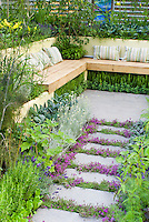 Thyme herbs in flower Thymus, in crevices and nooks and crannies of path stepping stones walkway with herbs and lettuce vegetables: rosemary Rosmarinus, Salvia officinalis, Lavandula lavender, dill, kale, patio, Garden benches with pillow cushions