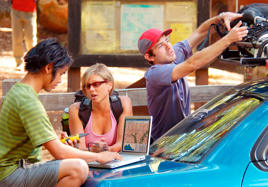 Friends planning an adventure trip with GPS and laptop computer.