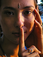 A portrait of a young woman with her forefinger over her lips and a bindi on her forehead, Hawai'i.