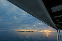 Looking across the ocean at sunset from a boat deck, Maldives.