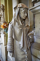 Picture and image of the realistic stone sculpture of a women praying at the monumental tomb of Luigi Priario by sculptor Paernio 1880,  the Staglieno Monumental Cemetery, Genoa, Italy
