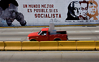 """A truck passes by a wall painting with the faces of Venezuelan President Hugo Chavez, Venezuelan independence heros Francisco de Miranda and Simon Bolivar and guerilla lider Che Guevara with a phrase reading """"a better world is possible, if it's socialist"""" in Caracas, Venezuela, on Saturday, Jul. 08, 2006. (ALTERPHOTOS/Alvaro Hernandez)"""