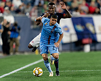 FOXBOROUGH, MA - SEPTEMBER 29: Ismael Tajouri-Shradi #29 of New York City FC dribbles as Cristian Penilla #70 of New England Revolution closely defends during a game between New York City FC and New England Revolution at Gillette Stadium on September 29, 2019 in Foxborough, Massachusetts.