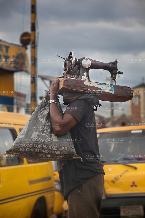 Nigeria. Enugu State. Enugu. Town center. An Igbo man carries a sewing machine on his shoulder.  A plastic bag with the words: Good for marketers, business and families.Traffic jam. Two yellow minibuse used for local transports. Enugu is the capital of Enugu State, located in southeastern Nigeria. 4.07.19 © 2019 Didier Ruef