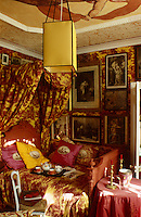 This pretty bedroom is decorated in toile de Jouy and the walls are lined with framed prints and engravings