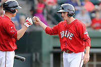 Shortstop Jimmy Rider (5) of the Greenville Drive is congratulated after scoring a run in a game against the Lexington Legends on Sunday, April 27, 2014, at Fluor Field at the West End in Greenville, South Carolina. Greenville won, 21-6. (Tom Priddy/Four Seam Images)