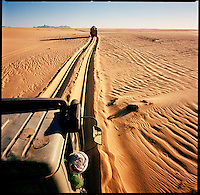 Sahara desert, Libya-Chad, November/December 2004..Every week, a convoy of 40 privately owned Libyan trucks loaded by the WFP with about 1000 metric tons of western food aid cross 2500 km of deep desert across Libya and Chad to reach more than 200 000 refugees from Darfur in camps near the Sudanese border. Crossing a soft sand area near Djebel Alweinat.