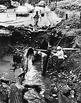 Utility crewmen tackle the job of repairing pipelines along East Aurora Street in Waterbury ruptured by flood waters that gouged out a deep trench in the roadway in July 1963.