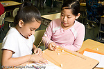 Education Elementary school Grade 5 class with science specialist making models from toothpicks and mini marshmallows two female students working together horizontal