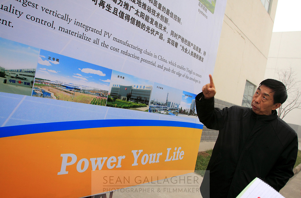 CHINA. Hebei.  Ma Xuelu, the president of the Low Carbon City Research Association of Baoding City points to a visitor display. The city is the world's first 'carbon positive' town. The town's main industires focus on producing wind and solar technologies. 2009