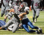 Claremont running back is wrestled to the ground by Northwood defender after a short gain.