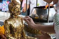 Bangkok, Thailand.  Worshiper Placing Gold Leaf on Buddha Statue, Royal Grand Palace Compound.