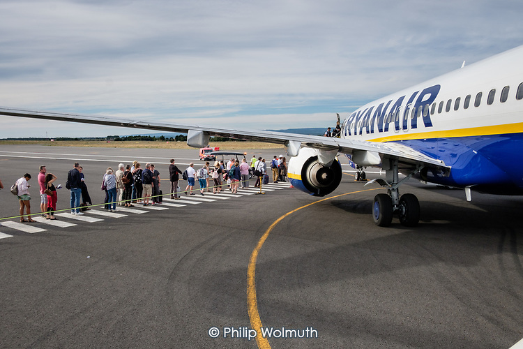 Passengers queue to board a Ryanair flight, Toulouse airport, France.