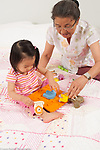 18 month old toddler girl with grandmother, working on puzzle, grandmother offering suggestions