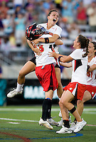 Karissa Taylor (20) of Maryland jumps into the arms of goalkeeper Brittany Dipper (43) as they celebrate the win with teammates Brandi Jones (4) and Abby Caso (31) at the NCAA Championship held in Johnny Unitas Stadium at Towson University in Towson, MD.  Maryland defeated Northwestern, 13-11, to win the title.